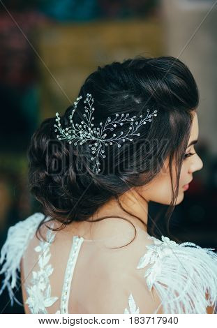 Elegant brunette bride sitting back with collected hair. Tender wedding stylish hairstyle with accessories.