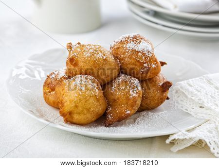 Sweet homemade beignets covered with powdered sugar.