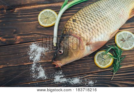 fish carp with lemon rosemary and onion on wooden background