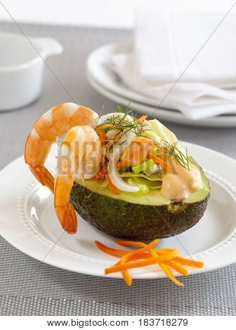 Avocado stuffed with shrimps and served with vegetables.