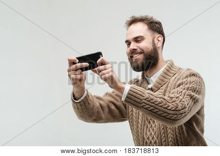 Isolated studio portrait of handsome young adult with beard taking photo with his smartphone