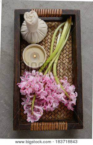 pink hyacinth flowers with candle, herbal ball in basket and towel on gray background