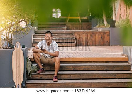 Portrait of a smiling young Asian man sending text messages on his cellphone while sitting alone on some stairs next to his long board outside