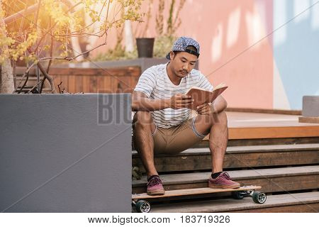 Casually dressed young Asian man in a cap reading a novel while sitting alone on some stairs with his long board outside
