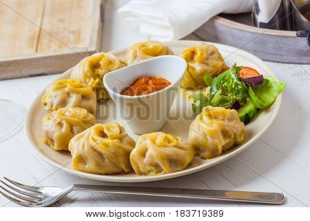 Nepalese traditional dumpling momos served with tomato chatni and fresh salad.