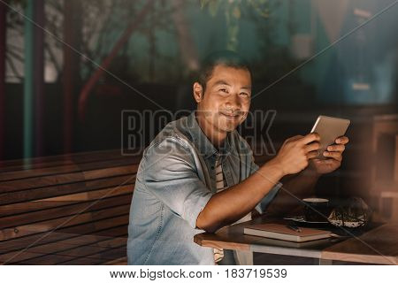 Portrait of a smiling young Asian man using a digital tablet while sitting alone in a cafe drinking a cup of coffee