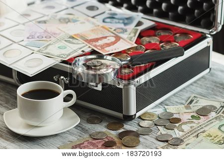 Different Collector's Coins And Banknotes With A Magnifying Glass, Box For Coins And Cup Of Coffee