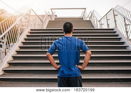 Rearview of a young man with his hands on his hips at the bottom of a long set of stairs while out for a run