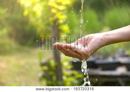 Water pouring in woman hand on nature background.