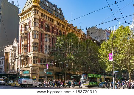 Melbourne Australia - April 03 2017: Melbourne city life. People crossing Collins street with traffic of cars and tram