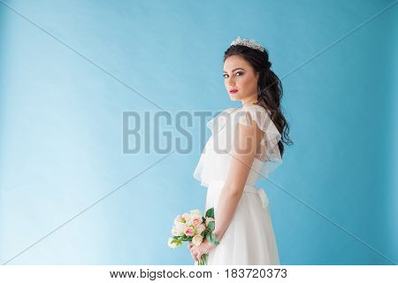Princess Bride in a white dress with a Crown on a blue background flower in hands