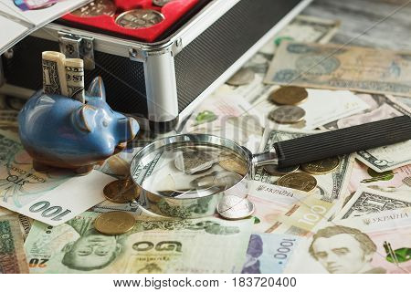 Different Collector's Coins And Banknotes In The Box, With A Magnifying Glass And Piggy Bank