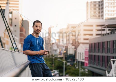 Portrait of a young Asian man in sportswear standing on a bridge listening to music on an mp3 player while out for a city run