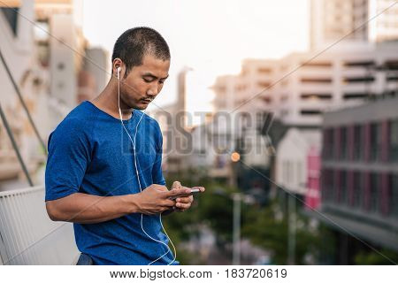 Fit young Asian man in sportswear standing on a bridge queueing up music on an mp3 player while out for a run in the city