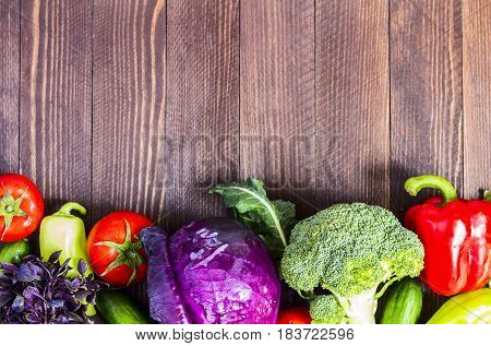Fresh vegetables red cabbage and broccoli cucumbers and peppers tomatoes and basil on dark wooden background. Farm organic products. Top view horizontal photo with space for text