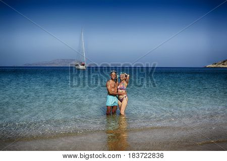 Beautiful couple in embrace on the beach in Greece