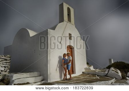 Couple woman and man in front of chapel Oia Santorini