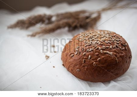 black round bread with seeds lying on a white table