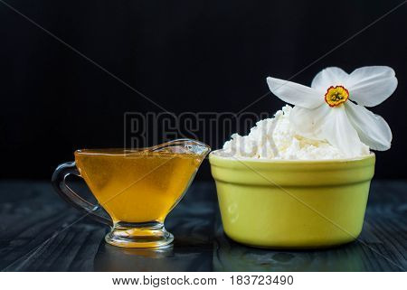 Honey and cottage cheese. A young cheese with honey and a flower. Cottage cheese in a deep plate and a glass jug with honey. Grainy cheese and honey on a dark background.