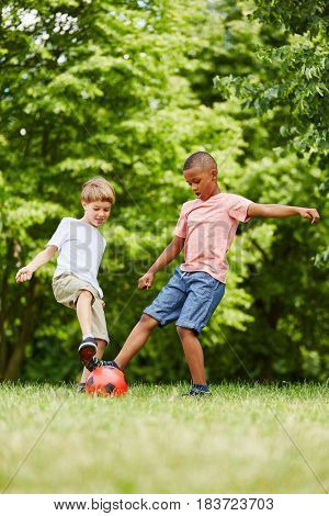 Kids practicing sport in summer playing soccer at the park