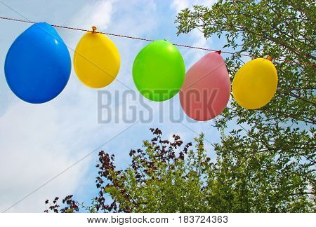 ready for the garden party, string of balloons in front of sky and trees