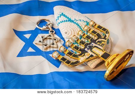 Jewish religious symbols: customary brimless kipa (kippah), menorah (a seven-lamp candelabrum), and a Star of David (Magen David) with Israeli flag on the background.