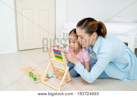 Mom is playing toys with daughter in the house.