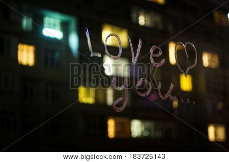 Love you inscription (text) by lipstick on the window glass in the night. Love concept. Valentine background and love confession.