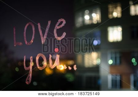 Love you inscription (text) by lipstick on the window glass in the night. Love concept. Valentine blurred background and love confession.