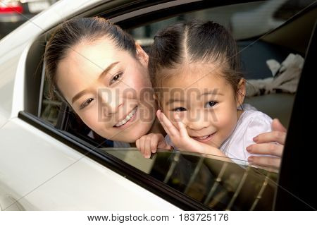Parents and daughters are happy with their cars.