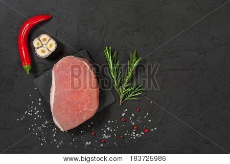 pork steak on a black stone with pepper