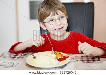 Adorable little school boy eating potato mash and chicken breast indoor. Blond child in domestic kitchen or in school canteen Cute kid and healthy food