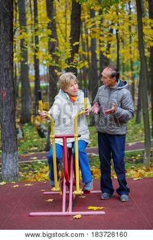 Elderly women is engaged on sport simulator and man talks with she in autumn park with fallen leaves