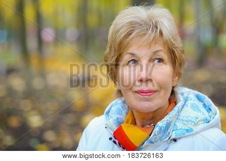 Elderly happy blonde woman looks up in autumn park, shallow dof