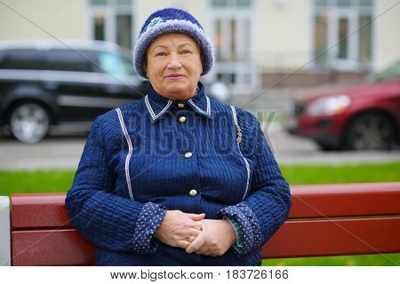 Elderly woman sits on bench near building at autumn day, shallow dof