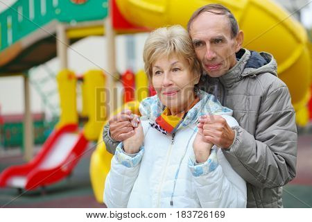 Elderly woman and man stand together on playground at autumn, shallow dof