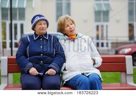 Two elderly women sit on bench near building and talk at autumn, shallow dof