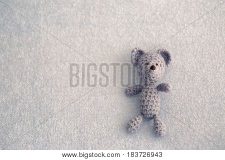 Blue teddy bear knitted toy lies on a blanket