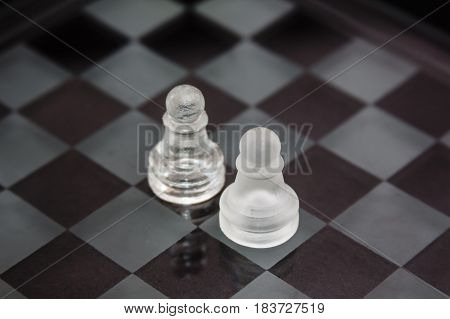 chess pieces made of glass: a confrontation between two pawns against a black background. Minimal business concept.