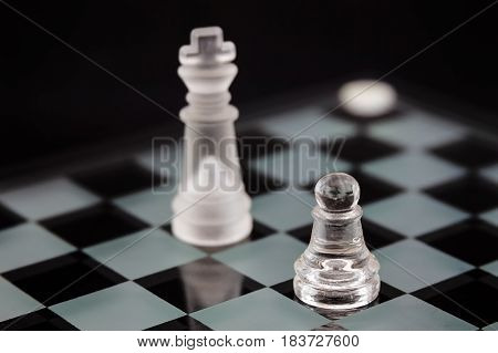 the chess pieces of glass: the opposition pawns and king on a black background. Minimal business concept.