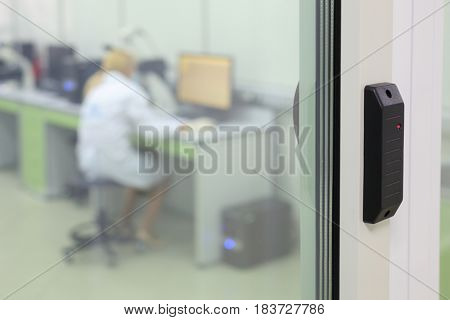 Device for access into modern office and working woman behind glass, shallow dof