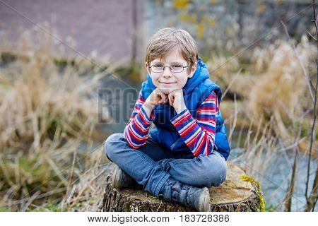 Active blond kid boy with casual colorful clothes and eye wear glasses sitting on tree stump on warm spring day. Happy child of 7 years enjyoing nature landscape.