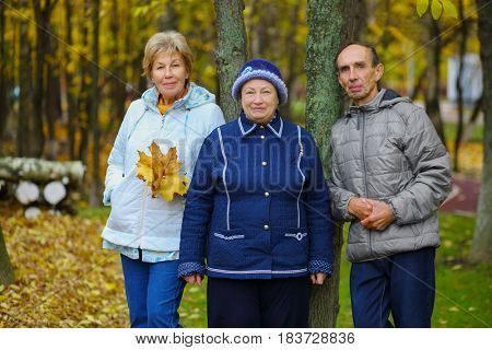 Elderly man and two women pose in fall dry park, shallow dof