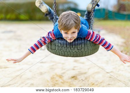 Funny kid boy having fun with chain swing on outdoor playground. child swinging on warm sunny spring or autumn day. Active leisure with kids. Boy wearing casual colorful school kid clothes