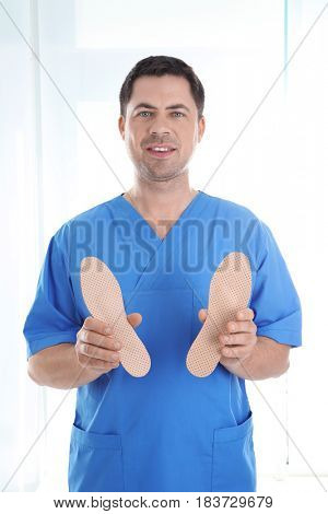 Male orthopedist with insoles on white background