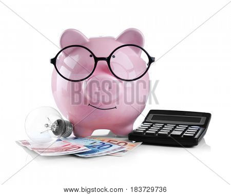 Cute pink piggy bank with glasses, money, bulb and calculator on white background