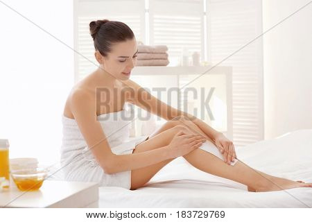 Young woman depilating legs with wax sitting on bed