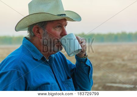Senior in cowboy hat drinking coffee while contemplating field in morning