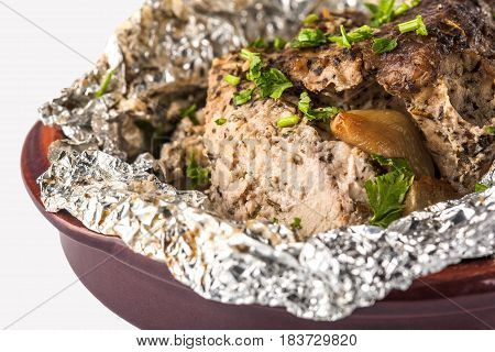 meat baked in foil with garlic in a plate