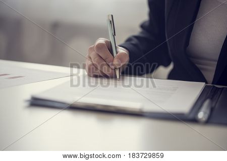 Retro vintage style image of a businesswoman signing a contract or document on a map.
